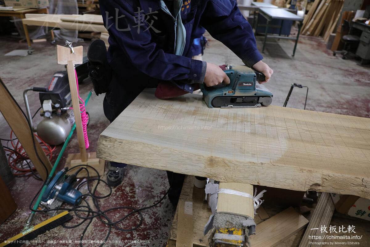 ベルトサンダーで、製材機の跡を削りながら反りを修正