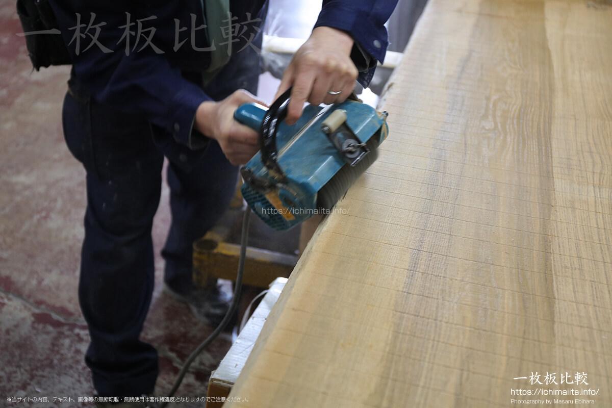 オービタルサンダーで一枚板の木場を削る