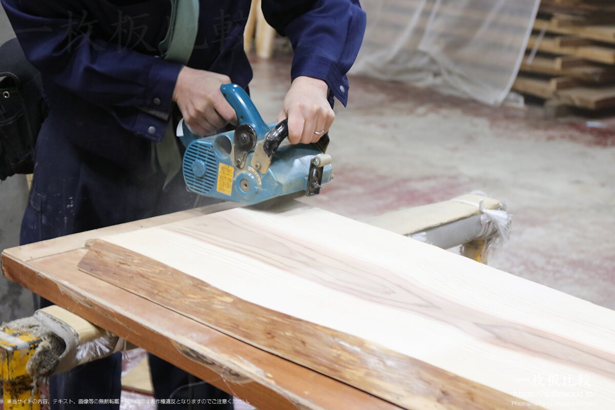 ホイールサンダーで杉の一枚板をうづくり加工している最中